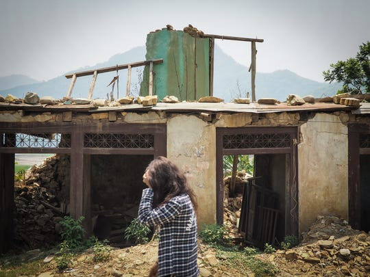 A girl walks past a house damaged by last year's massive