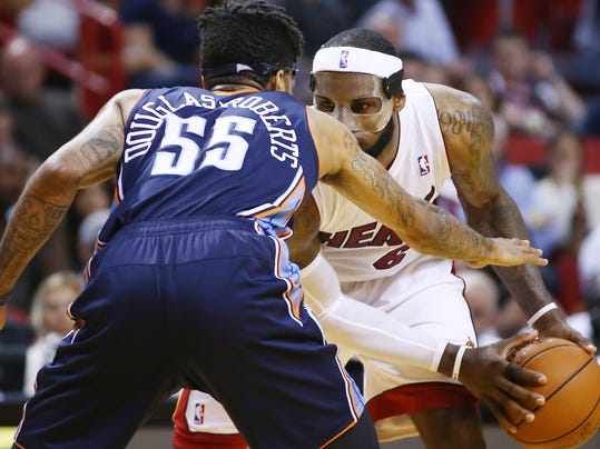 Charlotte Bobcats' Chris Douglas-Robert (55) tries to block Miami Heat's LeBron James (6) during the second half of an NBA basketball game in Miami, Monday, March 3, 2014. LeBron James scored a team recond of 61 points. The Heat won 124-107. (AP Photo/J Pat Carter)
