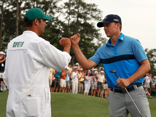 Jordan Spieth of the U.S. taps fists with his caddie Michael Greller after finishing the 18th hole during first round play of the Masters golf tournament at the Augusta National Golf Course in Augusta