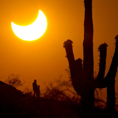 Hikers view a partial solar  eclipse in Papago Park