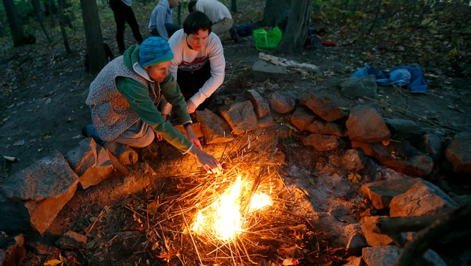 Rachel O'Donnell of Rochester and her sister Rivka Noll of Brighton gather next to a fire made during a survival skills beginner class using a friction method at Tryon Park.