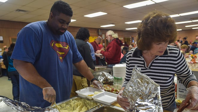 Tyree Sterling, left, scoops mashed potatoes onto a tray next to Linda Metcalfe, who is placing ham on another tray inside the Lemasters Comunnity Center on Thanksgiving Day. Both Sterling and Metcalfe are volunteers.