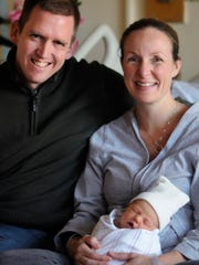 Matthew and Jennie Keane pose with newborn daughter Clare Elizabeth, born at 10:11 a.m. on Dec. 13 (or 12-13-14).