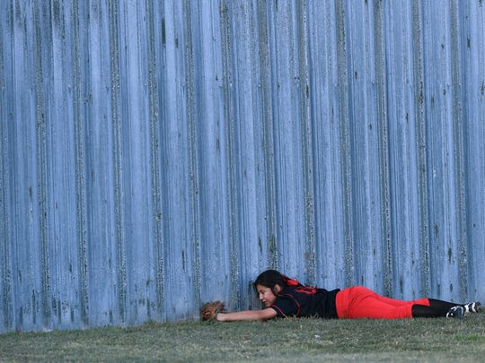 Colorado High School outfielder Alexa Garza rests her head against the outfield wall after successfully catching a fly ball Friday in Hawley. Her dive for the catch slid her across the grass up to the wall, but Garza seemed uninjured and continued playing. Colorado took two of the three games against Eastland.