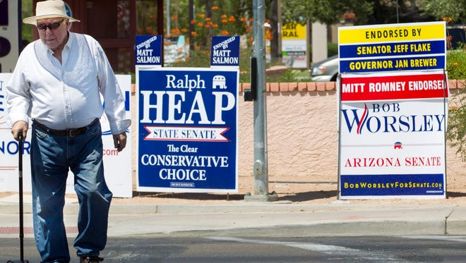 Mesa resident Denis LeBlanc passes campaign signs for Ralph Heap and Bob Worsley on Friday. Heap and Worsley, running for state Senate in District 25, are involved in a race using tricks that mirror previous elections for the same seat.