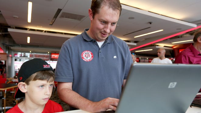 Will Kaiser, 9, watches his father, Travis, of Union, vote for his favorite players at the FOX Sports Ohio Champions Club at Great American Ball Park on June 29.