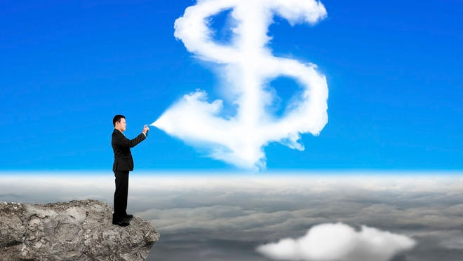 Businessman spraying dollar sign shape cloud paint on the cliff with cloudscape background