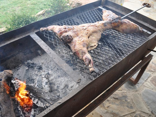 A whole spring lamb on an iron cross is slowly cooked over coals on an outdoor grill at Denton Valley Farms on May 19, 2017. Owners Amanda and Colby Hatchett sell lamb and goat meat, as well as beef, produce and other goods, at the store on their country property south of Clyde. They also host weddings and other special events at a 8,100-square-foot pavilion near their orchards.