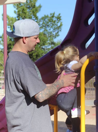 Drayton Witt helps his daughter, Ellie Mae Justice Witt, up the jungle gym at Rio Vista Community Park. Witt was 18 years old when he was accused of shaking his 4-month-old son to death. He served more than half of his sentence before new evidence led a Maricopa County Superior Court judge to dismiss his case.