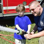 Gabe Allbritton, who was rescued from a 23-foot well Labor Day, uses a hose with assistance from Jonathan Alford of the Zetus Volunteer Fire Department. Gabe was promised a pizza party and fire engine ride during his rescue.
