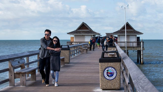 A young couple huddles together to stay warm while walking along the Naples Pier on Tuesday, Jan. 2, 2018.