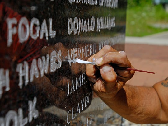 Union laborer Martin Esquibel works on restoring names Monday, Aug 1, at the Tunnel Explosion Memorial at Fort Gratiot County Park.