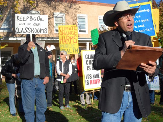 Roman Catholic Pastor Vincent Paul Chavez, right, of the Saint Therese school and parish in Albuquerque, protests proposed state science standards on behalf of the Santa Fe Archdiocese outside a public hearing in Santa Fe, N.M., Monday, Oct. 16, 2017. The proposed standards for public schools has come under intense criticism for omitting or deleting references to global warming, evolution and the age of the Earth. Comments at the hearing overwhelmingly sided against state revisions to a set of standards developed by a consortium of states and the National Academy of Sciences.