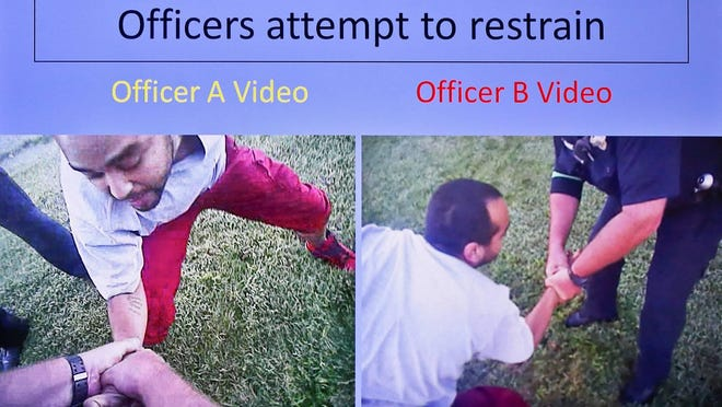 This image taken from Topeka police body camera video shows officers struggling with Dominique White, who had a handgun in his pocket, before he broke free, started to run away and was fatally shot in September 2017.
