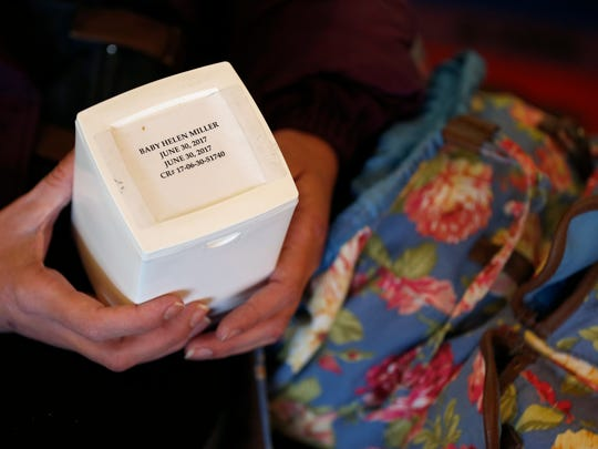"Mirenda Barrows holds the ashes of her baby Helen Mae on Wednesday, March 7, 2018. Barrows was six months pregnant at the time of the accident and the infant was delivered via emergency c-section but did not survive. She keeps Helen's ashes in the floral backpack she carries every day. ""I don't want anything to happen to her again,"" Barrows said."