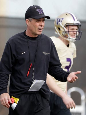 Washington head coach Chris Petersen, left, walks on the field next to quarterback Jake Browning during a Peach Bowl NCAA college football practice.
