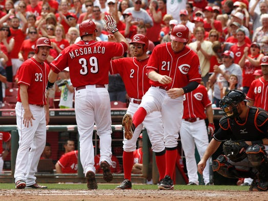Cincinnati Reds' Devin Mesoraco (39) is congratulated  by Todd Frazier (21) Zack Cozart (2) and Jay Bruce (32) after Mesoraco hit a grand slam off Miami Marlins starting pitcher Brad Hand  in the fifth inning of a baseball game, Sunday.