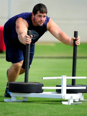 Titans guard Andy Levitre, recovering from an appendectomy, pushes a weighted sled before his teammates begin practice at Saint Thomas Sports Park on Thursday.