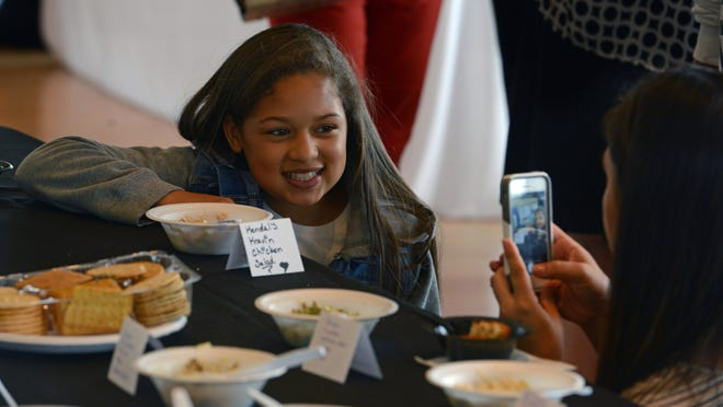Kendal Harper, 10, gets her photo taken with her creation Sunday during the Junior League of Pensacola's third annual Dish It Out, at the Corrine Jones Community Center. The even is a tasting and shopping showcase for people who love to eat, cook and entertain.