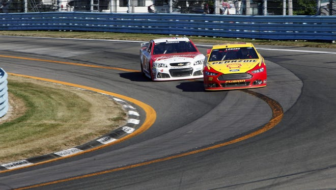 Joey Logano (22) passes Kevin Harvick (4) on the last turn on the way to winning the Cheez-It 355 NASCAR Sprint Cup Series race at Watkins Glen International on Aug. 9, 2015 in Watkins Glen.