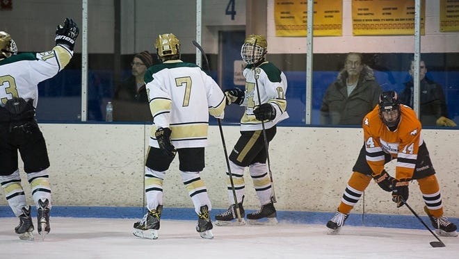 Sheldon Sturos (17) celebrates Howell's only goal with Russell Daavettila (left) and Josh Seiter (7).