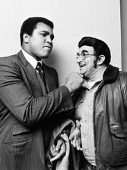 Muhammad Ali plays around with a fan as he arrives