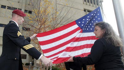 Northern Kentucky University students Sgt. Brian Collins (Ret.), left and former Army Pfc. Audrey Thurston unfurl the flag as it is raised at a Veterans Day ceremony at NKU.
