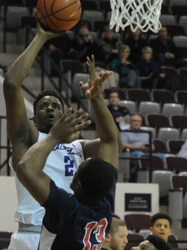 ACU's Jalone Friday, left, shoots over Arlington Baptist's