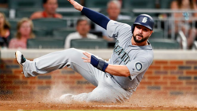 Yonder Alonso avoids the tag at home to score in the fourth inning of the Mariners' 6-5 win over Atlanta on Monday.