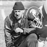 Buck Nystrom works with a Michigan State football player.