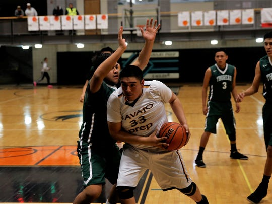 Navajo Prep's Tyler Pete, No. 33 in white, fights his way into the paint against Thoreau's Gene Hosteen, No. 53 in green, during Thursday's District 1-4A tournament semifinals at NPS.