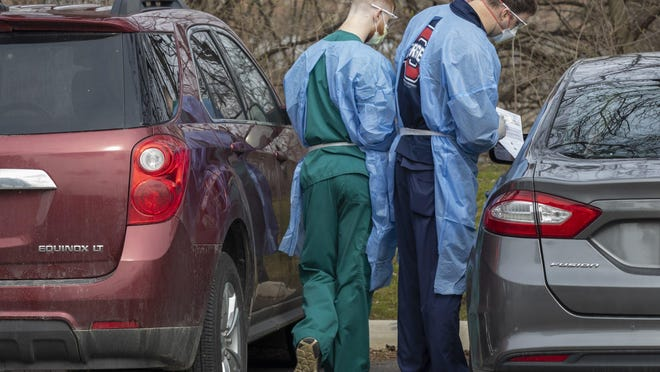 Employees outside an Ohio State University building  perform coronavirus testing on a patient inside a car.