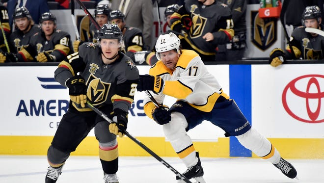 Vegas Golden Knights center Cody Eakin (21) skates with the puck under pressure from Nashville Predators left wing Scott Hartnell during the first period of an NHL hockey game Tuesday, Jan. 2, 2018, in Las Vegas. (AP Photo/David Becker)
