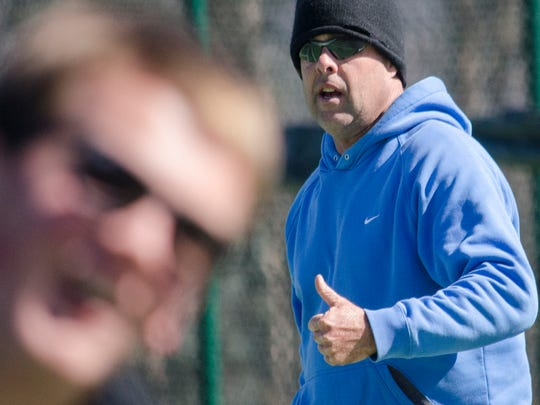Warlassies tennis coach Chris Barcklow runs the boys team through practice drills.