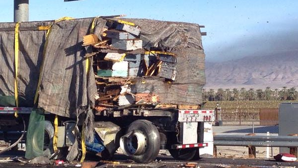 Bees begin to fly out of their containers after a semi truck carrying bees and a semi truck carrying frozen chicken collided on I-10 near Coachella on Monday morning.