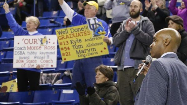 Delaware head coach Monte Ross addresses the crowd, some holding signs supporting him, after the last home game of the season, a 83-75 loss in overtime to Elon at the Bob Carpenter Center Saturday.