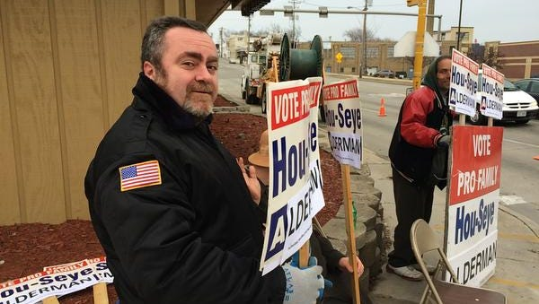 Job Hou-Seye, left, holds a sign at 14th and Erie with a nearby Mark Hermann, right, election day Tuesday April 7, 2015 in Sheboygan.  Hou-Seye is running to replace Kevin Matichek as alderman.