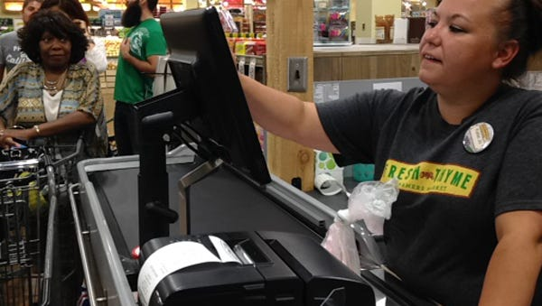 A cashier at Fresh Thyme in East Lansing rings up groceries at the end of the Lettuce Live Well grocery store tour Monday.