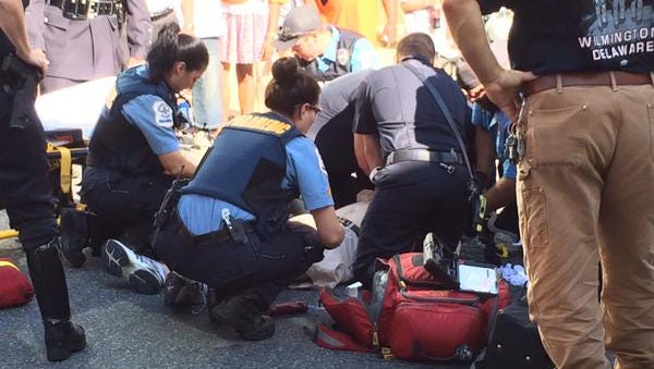 Paramedics and police treat a man who collapsed on King Street at the start of the Labor Day parade.