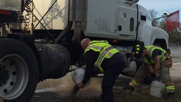 Officials respond to the area where a semitrailer leaked hydraulic fluid on Interstate 65 northbound Friday evening.