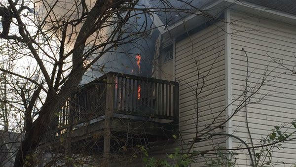 Smoke billows from a still-burning house fire in Muncie on Friday afternoon.