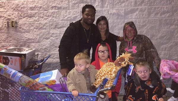 Vontaze Burfict takes a family on a shopping spree at Toys 'R Us in Florence, Kentucky.