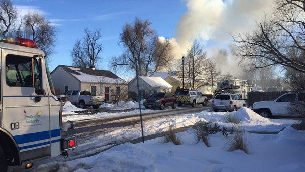 Smoke billows out of a garage at 618 Lesser Dr. Saturday afternoon. Poudre Fire Authority responded to the two-alarm fire shortly after 3 p.m.