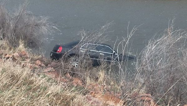 A vehicle is shown submerged in Skunk Creek on Tuesday afternoon.