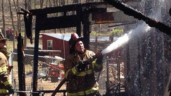Firefighters extinguish hot-spots at a fire on Steigerwalt Hollow Drive in Fairview Township.