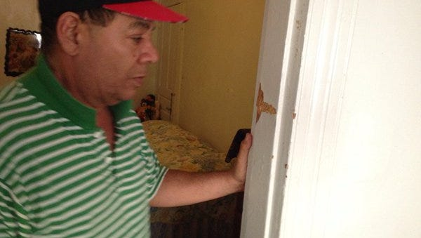 Carlos A. Burgos-Moya shows where a bullet struck his door jamb at his home on South Pine Street, York, on Sunday.