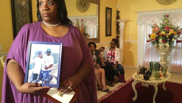 """""""He loved to fish,"""" said niece Beverly Bell-Barber as she holds an old photo of Willis Bell with his wife inside their home."""