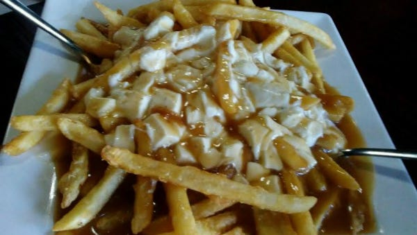 Artisan Cafe's poutine, a Canadian dish, is a heaping pile of crisp french fries with brown gravy and slightly melted cheese curds.