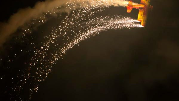 Aerobatic pilots paint the sky with light during the Saturday night air show over the EAA grounds July 29, 2017. Pictured performing is pilot Gene Soucy.