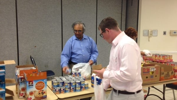 """Mike Hickey, president of the Rotary Club of Orchid Island and volunteer Dr. Kassamali Jamal sort and package the food each Wednesday for the """"Weekend Food for Kids"""" program. Kid-friendly food like peanut butter and applesauce are distributed each week in five elementary schools to needy children in Indian River County."""